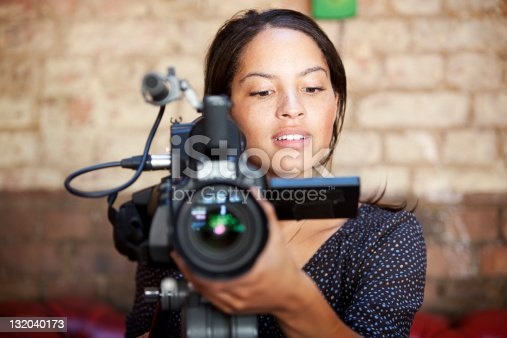A look of content concentration on the face of a pretty camera operator pleased with the results of her shoot.