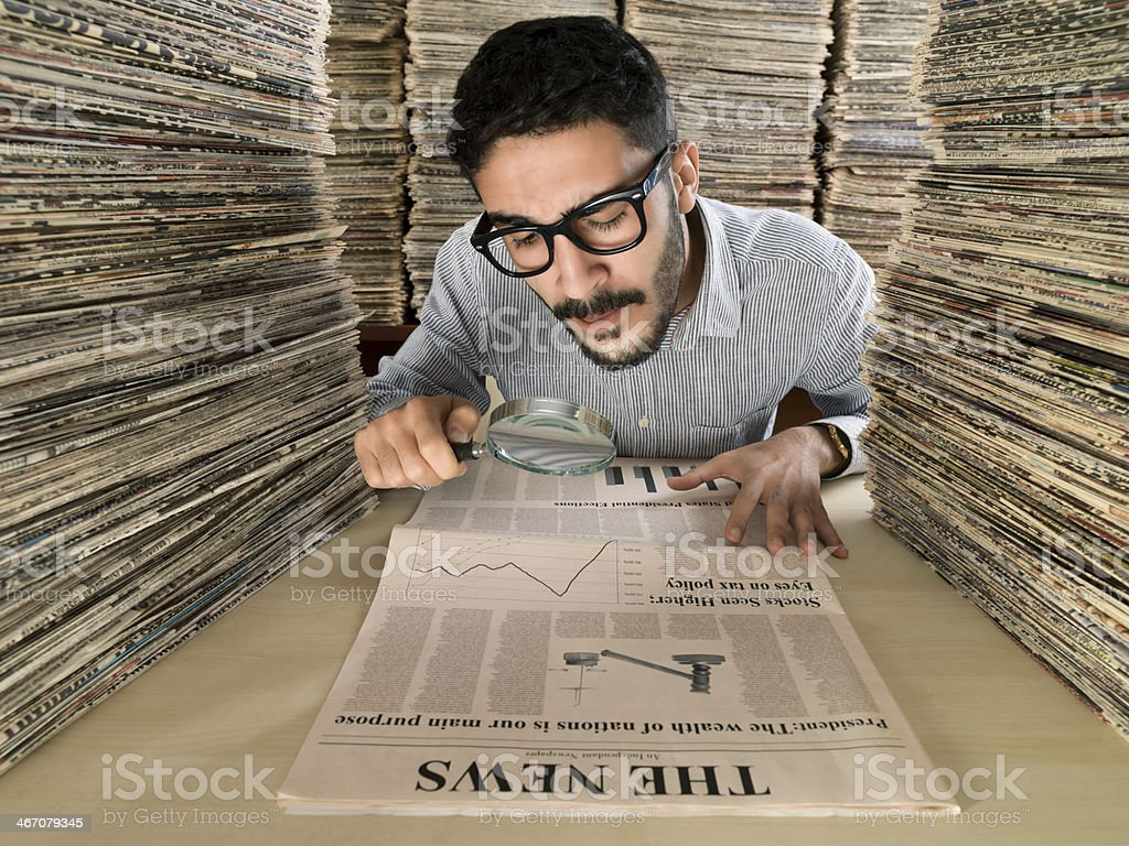 Media consultant looking at newspaper through magnifying glasses stock photo