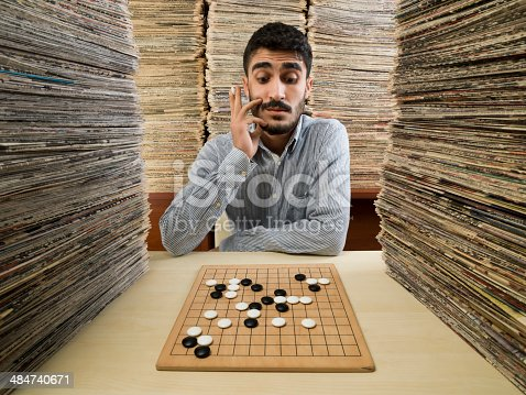 Young man with mustache and black hair sitting on desk in an archive library and playing go game.He is holding a stone in right hand.He is wearing a gray shirt.Large stack of newspapers or papers on the background and on the desk.Shot in studio with a medium forma camera Hasselblad H4D.
