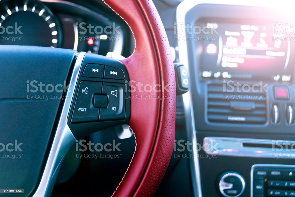 Media control buttons on the red steering wheel in black leather with computer monitor, modern car interior. Soft lighting. Abstract view stock photo