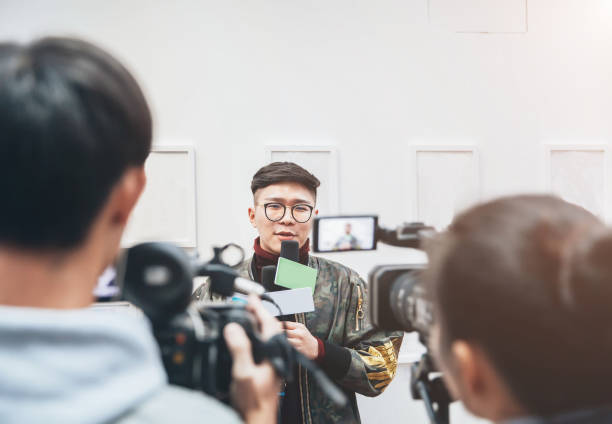 TV Media Interview Artist introducing arts to visitors in Beijing,China. publicity event stock pictures, royalty-free photos & images