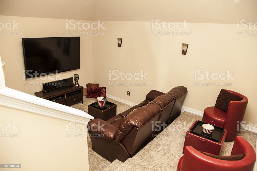 Media room in upscale, new home. Large TV, sofa, seating. stock photo