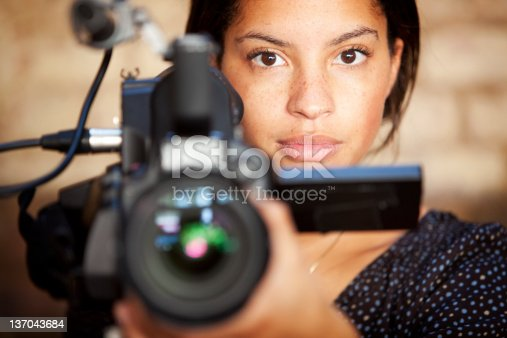 A confident glance from a video camera operator engaging eye contact with her subject during filming.