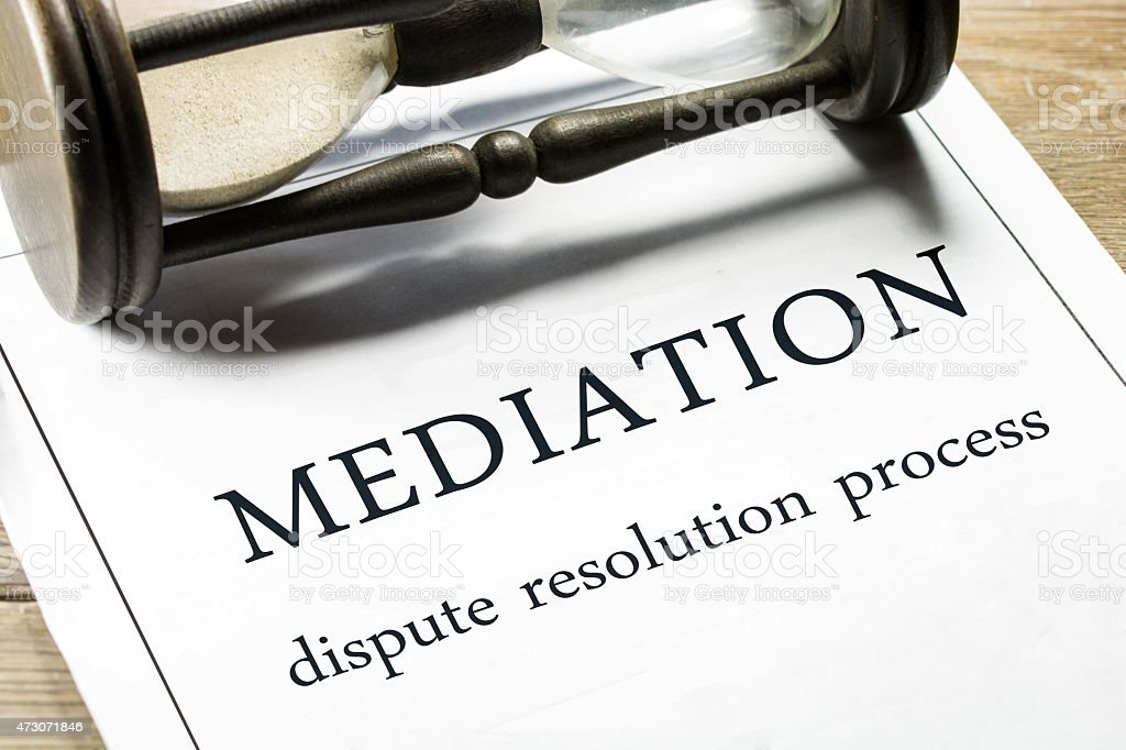 Mediation guideline papers with a sand clock placed sideways stock photo