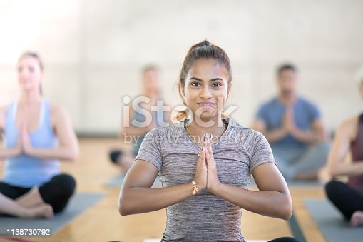 A very diverse group of friends workout one day together. While sitting in prayer pose, a woman has her eyes open and hands together.