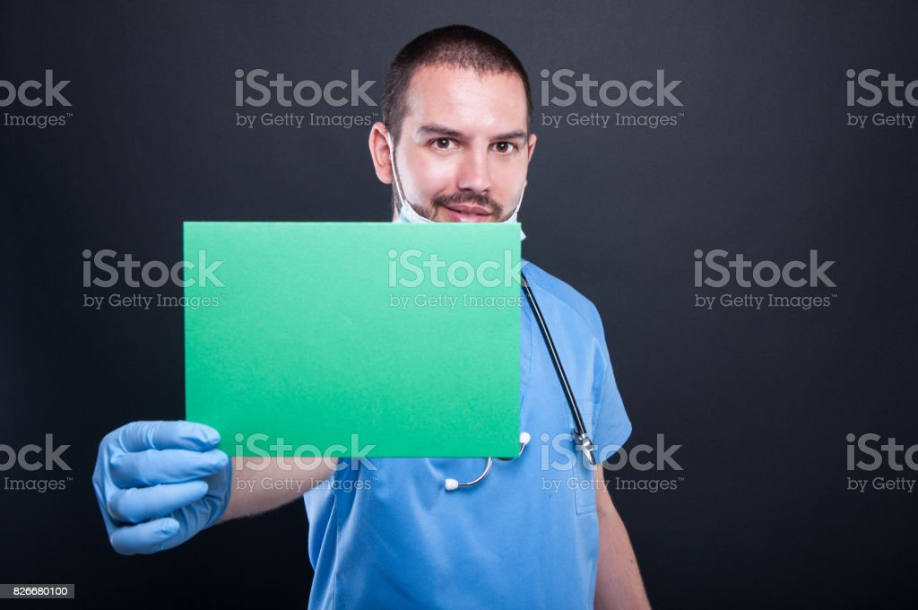 Medic holding and showing green copypsace card stock photo