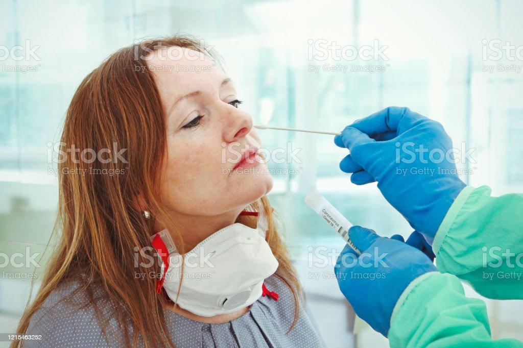 Medic taking sample for coronavirus testing Medic taking sample from patients nose for coronavirus testing Adult Stock Photo