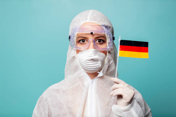medic woman wearing protective clothing against the virus holds Germany flag stock photo