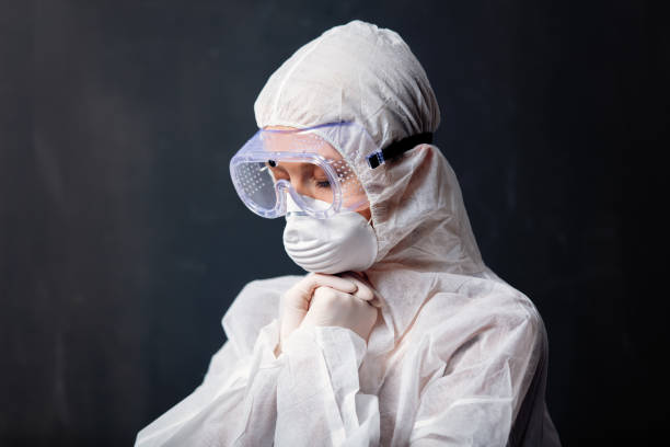 medic woman wearing protective clothing against the virus is pray stock photo