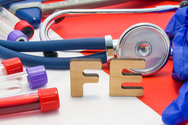 fe medical abbreviation meaning total iron or ferrum in blood in laboratory diagnostics on red background. chemical name of fe is surrounded by medical laboratory test tubes with blood, stethoscope - anemia foto e immagini stock