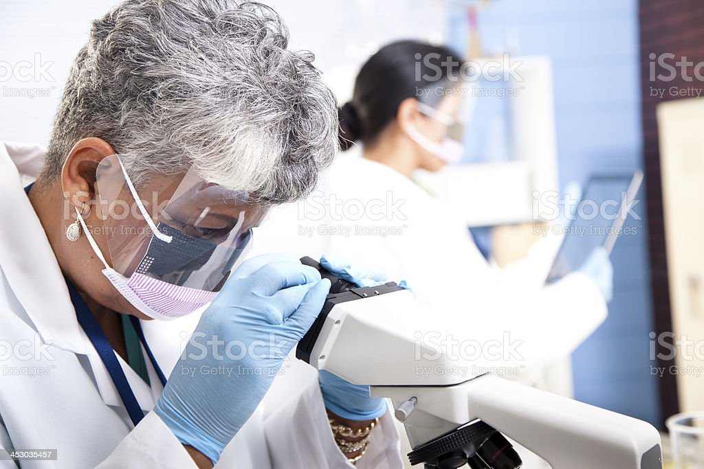 Medical: Adult female scientist looks through microscope. Scientific research. royalty-free stock photo