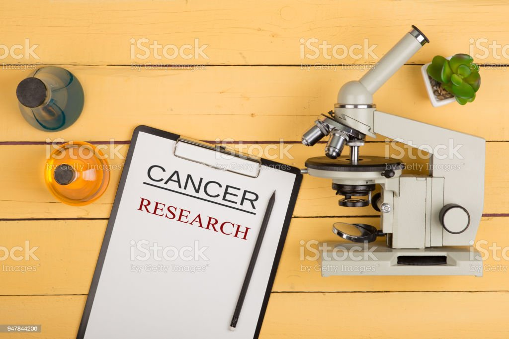 Medical and science concept - microscope, clipboard with text 'Cancer research' and chemical liquids on the yellow desk in the auditorium stock photo
