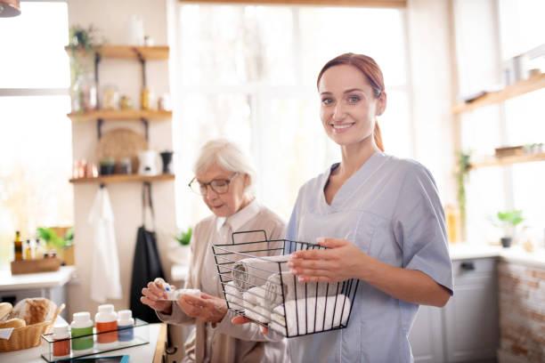 medische begeleider staande in de buurt van gepensioneerde draag bril - thuiszorg stockfoto's en -beelden