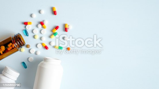 Medical bottles and medication pills spilling out on to pastel blue background. Top view with copy space. Healthcare, pharmacy, medicine concept