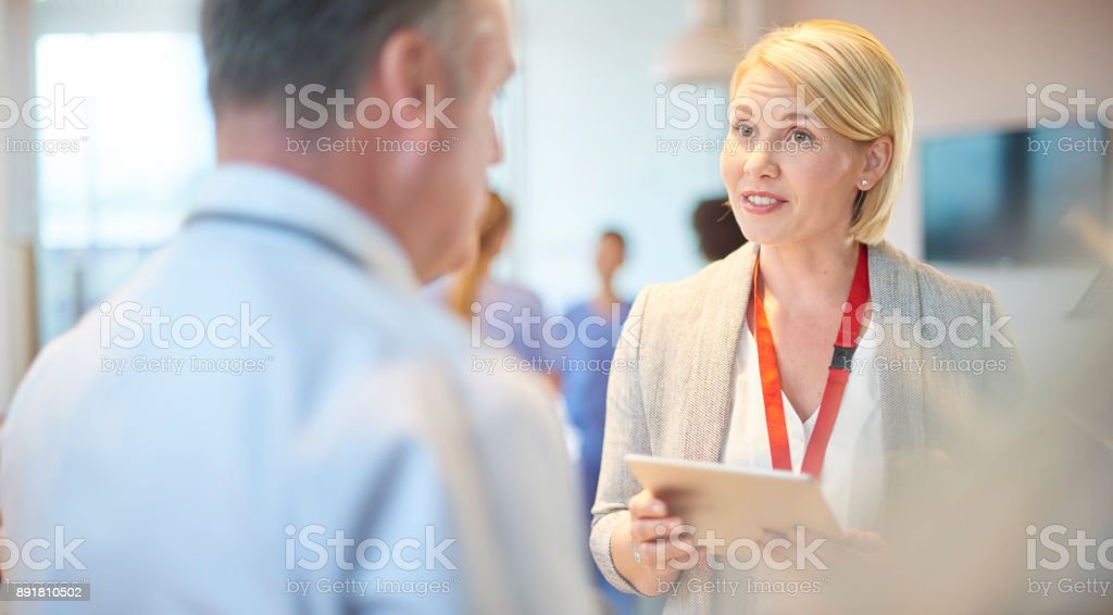 a female doctor chats to a colleague on the ward