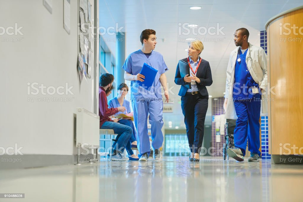 a mid adult male doctor speaks with a businesswoman , sales person on...