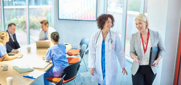medical business relationship a businesswoman chats with a doctor as they leave a boardroom meeting in a hospital administrator stock pictures, royalty-free photos & images