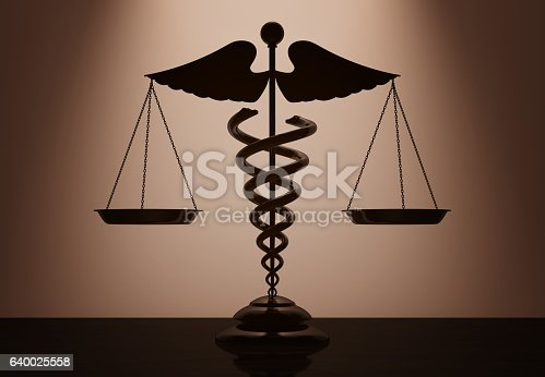 istock Medical Caduceus Symbol as Scales with backlight over Wall 640025558