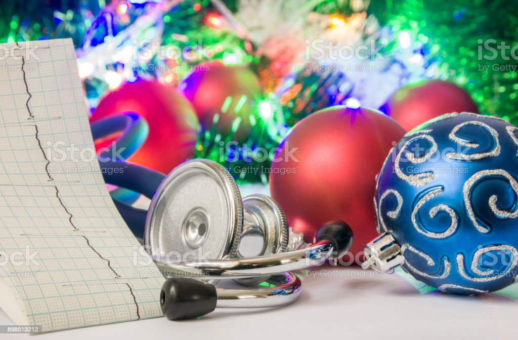 Medical cardiology Christmas and New Year photo - stethoscope and electrocardiogram tape are located near balls for Christmas tree in blurry background with electric garlands lights and toys stock photo