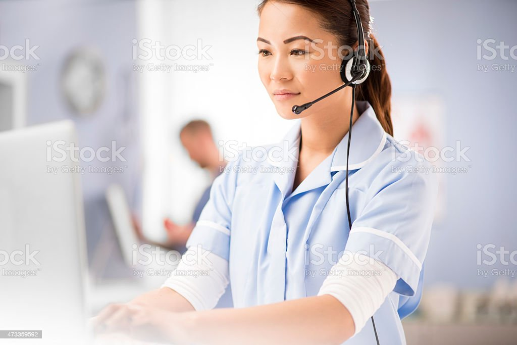 a young female nurse talks into a headset . She is wearing medical...
