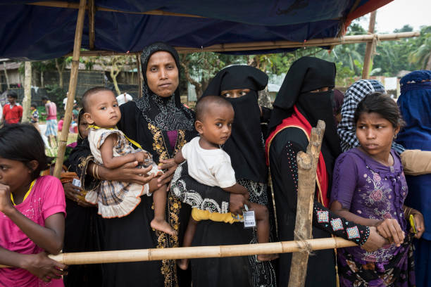 Medical check-up for Rohingya children at refugee camp in Bangladesh Rohingya women and children wait in line for the children to have a mdeical check-up at a field hospital at Chakmarkul refugee camp, Bangladesh (October 28, 2017) rohingya culture stock pictures, royalty-free photos & images