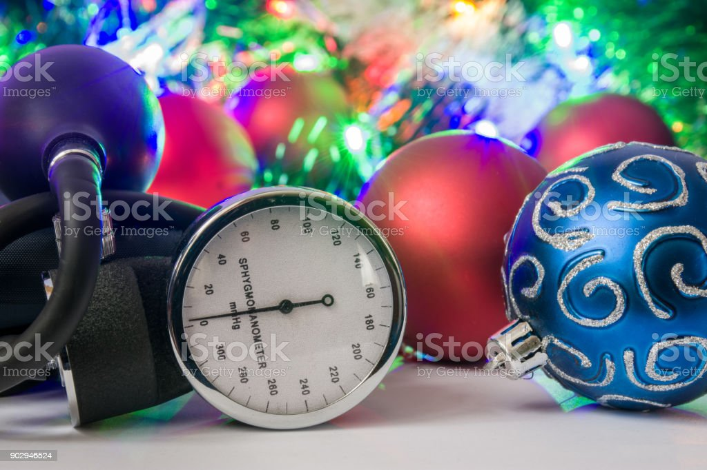Medical Christmas and New Year photo - blood pressure gauge or sphygmomanometer are located near balls for Christmas tree in blurry background with electric garlands lights and toys stock photo