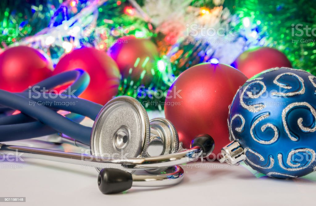 Medical Christmas and New Year photo - stethoscope or phonendoscope are located near balls for Christmas tree in blurry background with electric garlands lights and toys stock photo