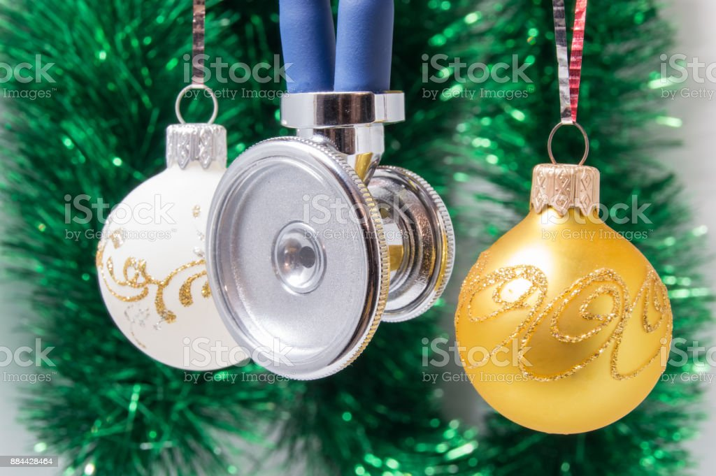 Medical Christmas and New Year. Stethoscope surrounded by white and gold christmas tree balls with blurred christmas decoration on background - green garlands. Concept for the New Year in medicine stock photo