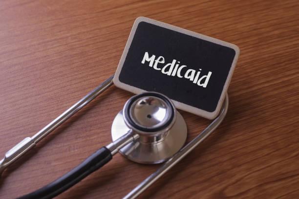 Medizinisches Konzept - Medicaid Wort auf Label-Tag mit Stethoskop auf Holz Hintergrund geschrieben. – Foto