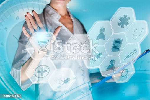 istock Medical concept of futuristic health care technology and augmented reality. A female doctor hand is touching a virtual control panel. Communicate about innovative use of future health care technology 1056482262