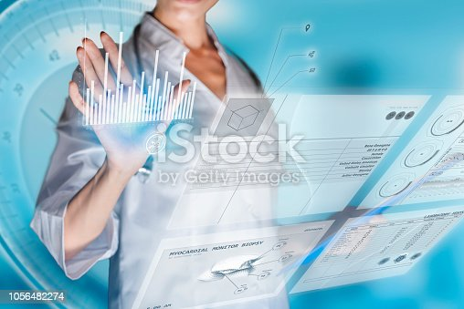 istock Medical concept of futuristic health care technology and augmented reality. A female doctor hand is touching a virtual innovative control panel to monitor a patient's electronic health records 1056482274