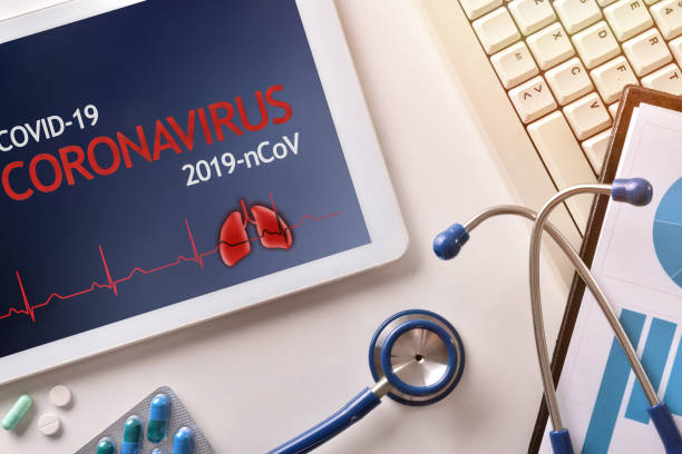 Medical desk with tablet with coronavirus title and supplies stock photo