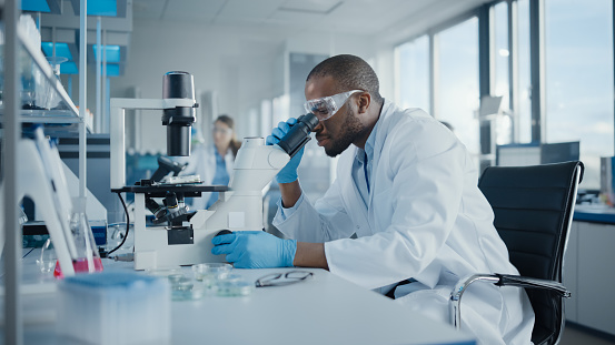 Medical Development Laboratory: Portrait of Black Male Scientist Looking Under Microscope, Analyzing Petri Dish Sample. Professionals Doing Research in Advanced Scientific Lab. Side View Shot