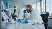 istock Medical Development Laboratory: Portrait of Black Male Scientist Looking Under Microscope, Analyzing Petri Dish Sample. Professionals Doing Research in Advanced Scientific Lab. Side View Shot 1293772875