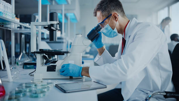 Medical Development Laboratory: Scientist Wearing Face Mask Looking Under Microscope and Using Digital Tablet. Specialists Working on Medicine, Biotechnology Research in Advanced Pharma Lab stock photo