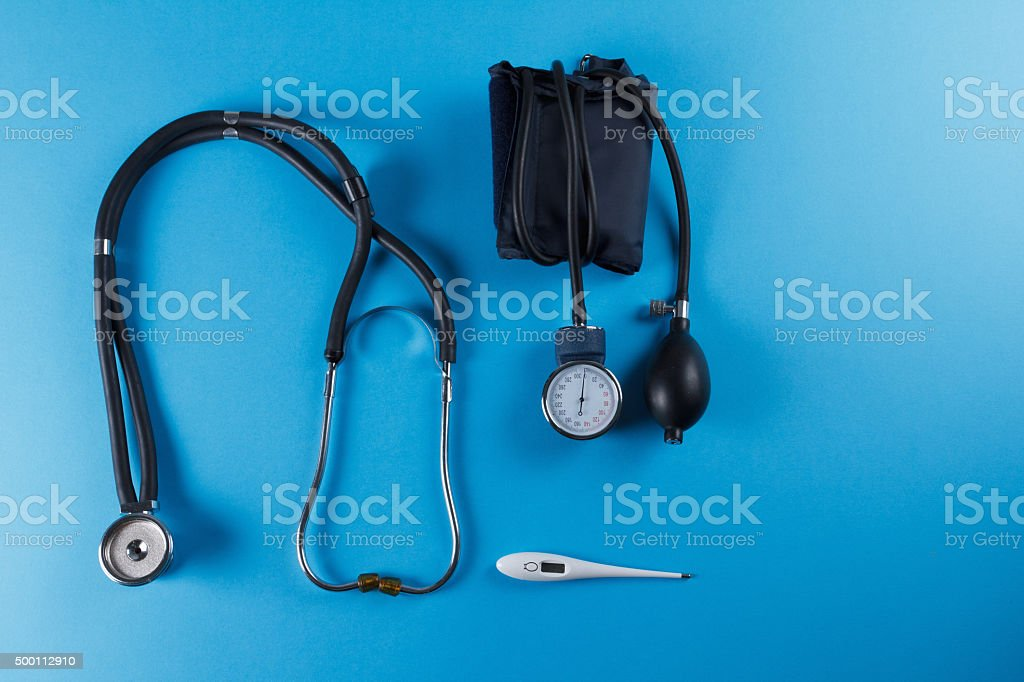 Medical devices stethoscope, tonometer, and thermometer stock photo