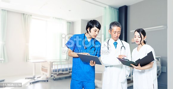Medical doctor and nurses in sickroom.