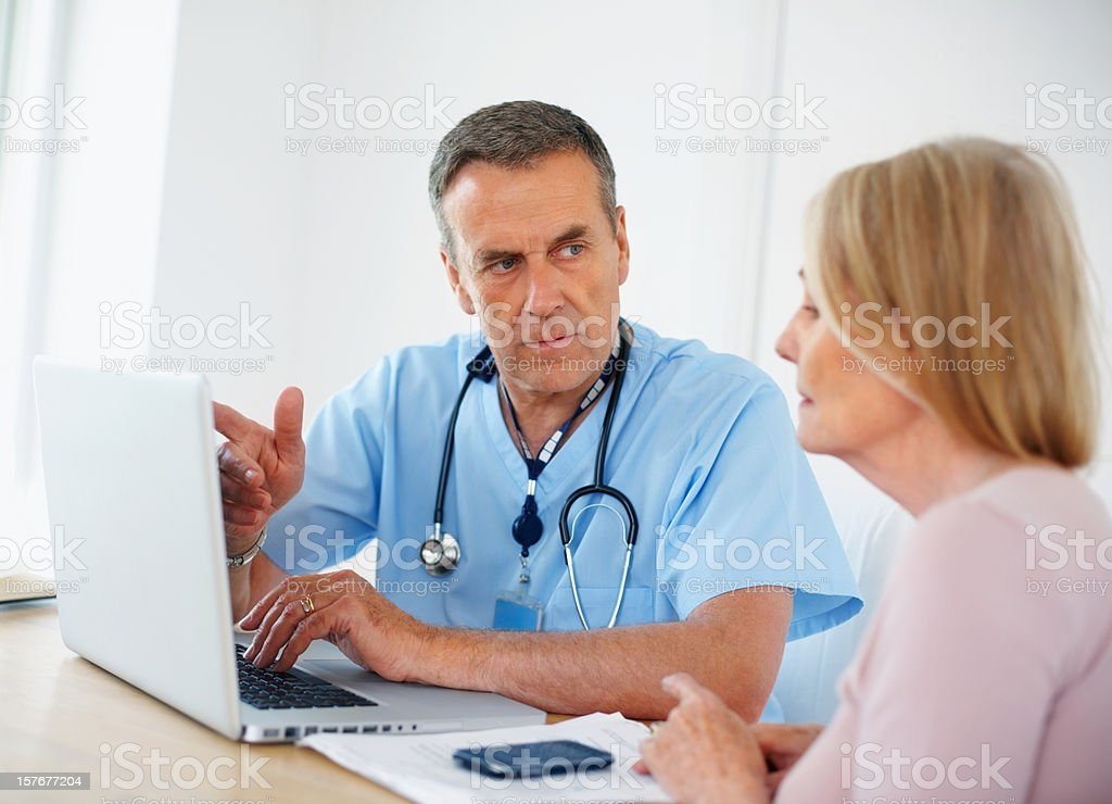 Medical doctor discussing with female patient using laptop royalty-free stock photo