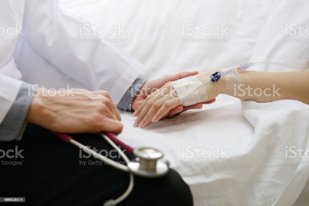 Medical doctor holding patient's hand and comforting her royalty free stockfoto