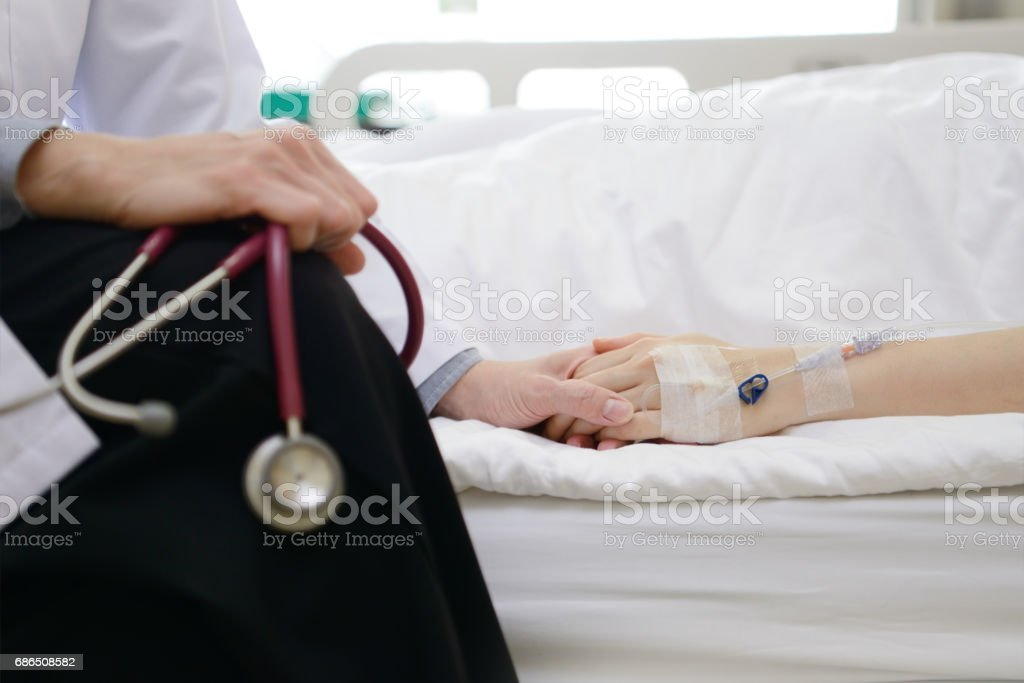 Medical doctor holding patient's hand and comforting her foto stock royalty-free