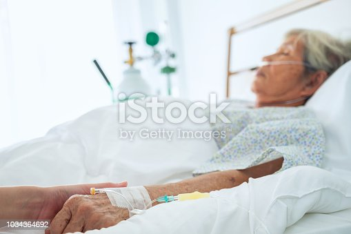 958891774istockphoto medical doctor holing senior patient's hands and comforting her, Hand of man touching senior woman in clinic, care for the elderly concept 1034364692