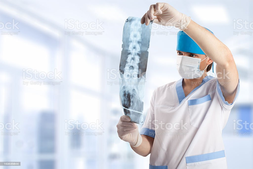 medical doctor looking at x-ray picture of spine stock photo