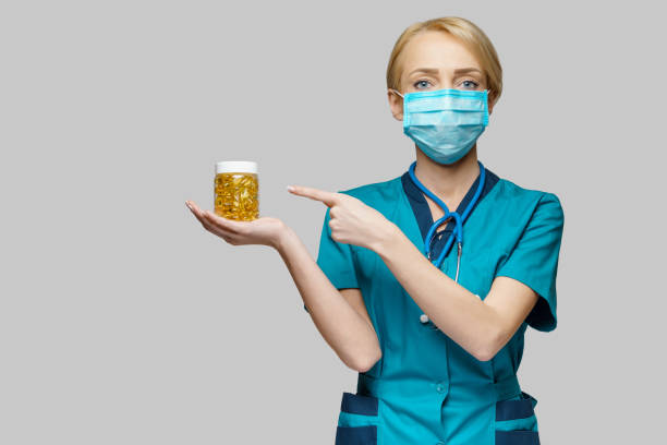 medical doctor nurse woman wearing protective mask and rubber or latex gloves - holding can of pills stock photo