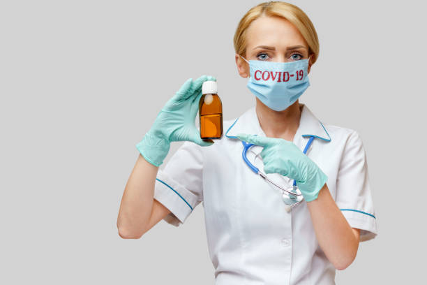 medical doctor nurse woman wearing protective mask and rubber or latex gloves - holding bottle of cough syrup stock photo
