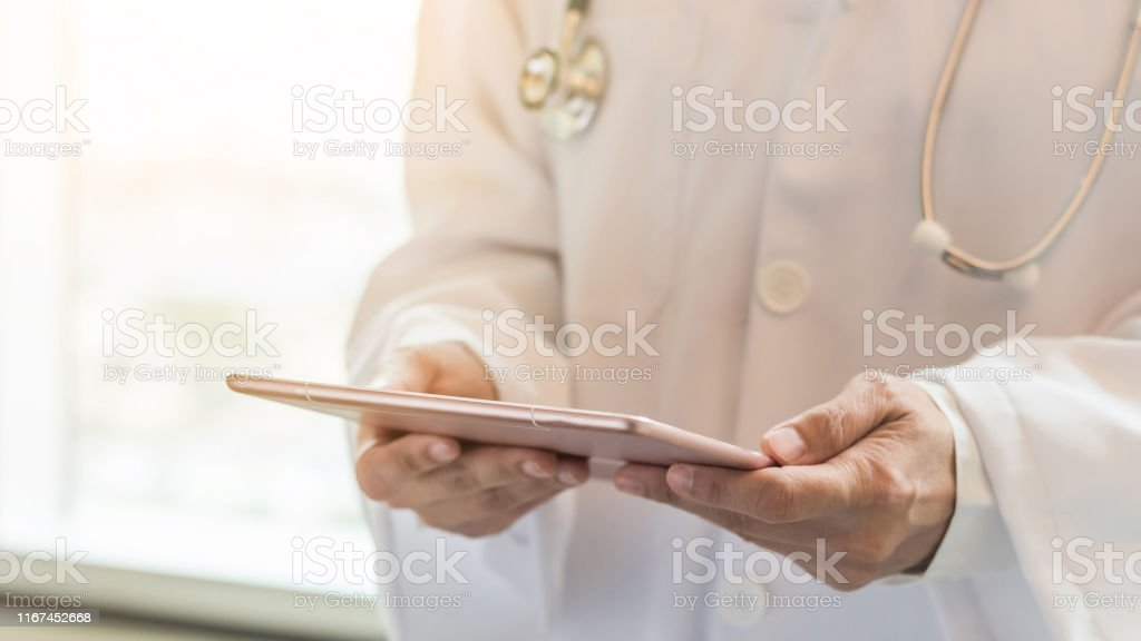 Medical doctor or physician with tablet for patient\'s health record...