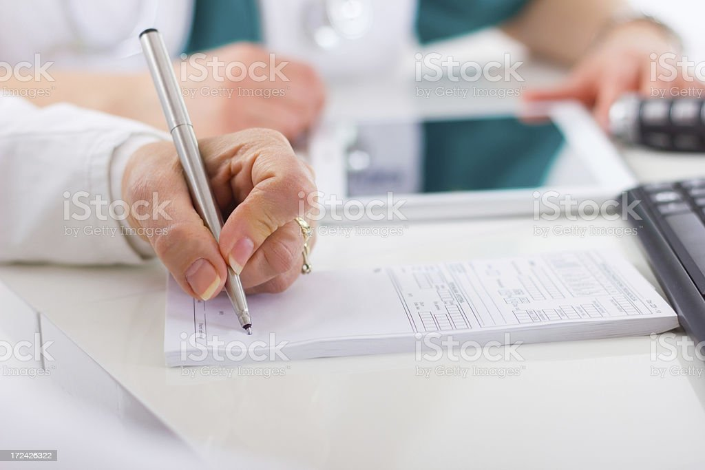 Medical doctor signing a prescription form royalty-free stock photo