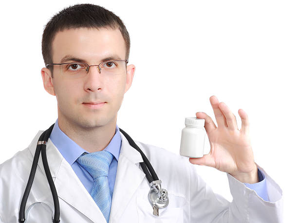 Medical doctor with blank pill's bottle. Isolated stock photo