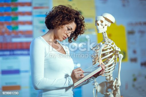 istock Medical doctor woman teaching anatomy using human skeleton model 929961230
