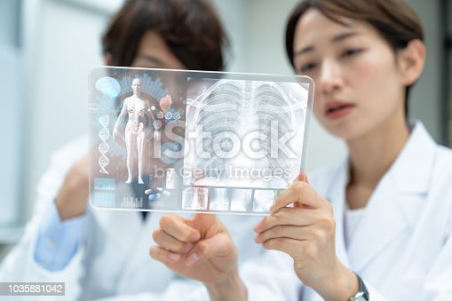 864464934istockphoto Medical doctors looking a futuristic tablet device. Electronic medical records. 1035881042