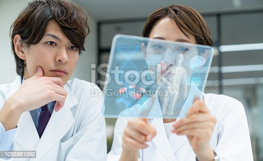 864464934istockphoto Medical doctors looking a futuristic tablet device. Electronic medical records. 1035881050